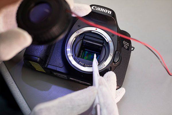 A specialist cleaning the sensor on a Canon EOS camera